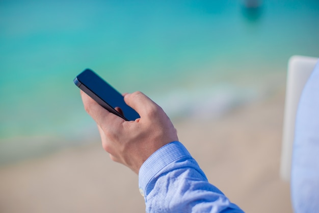 Geschäftsmann mit telefon in der hand an einem tropischen strand