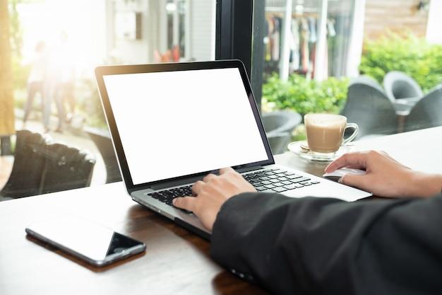 Geschäftsmann mit und auf laptop mit leeren weißen bildschirm und kaffeetasse schreiben