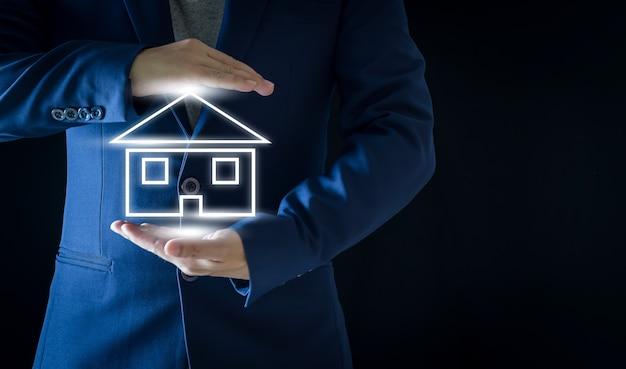 Geschäftsmann mit weiß leuchtendem haussymbol auf schwarzem hintergrund immobilien- und finanzkonzepte