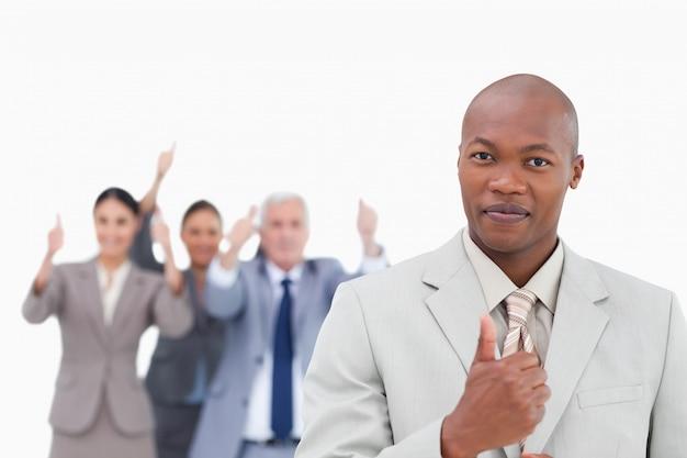 Geschäftsmann mit zujubelndem team hinter ihm daumen auflassend