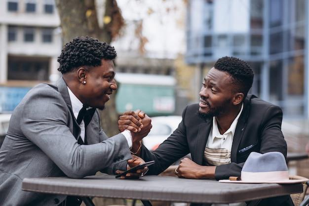 Geschäftsmann mit zwei afrikanern, der außerhalb des cafés sitzt
