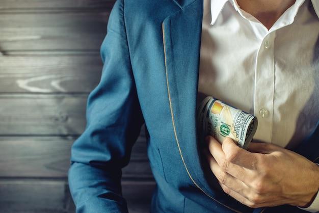 Geschäftsmann, mitglied oder offizier steckt ein bestechungsgeld in die tasche