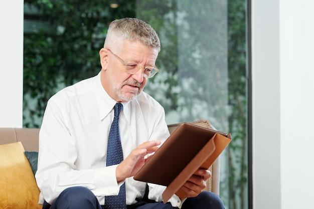 Geschäftsmann mittleren alters, der artikel oder dokument auf tablet-computer liest