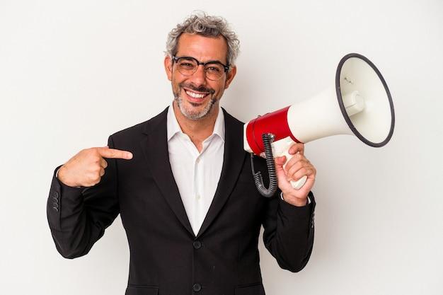 Geschäftsmann mittleren alters, der ein megaphon isoliert auf weißem hintergrund hält, der mit der hand auf einen hemdkopierraum zeigt, stolz und selbstbewusst