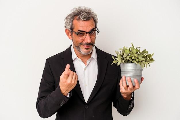 Geschäftsmann mittleren alters, der eine pflanze hält, die auf weißem hintergrund isoliert ist und mit dem finger auf sie zeigt, als ob er einladen würde, näher zu kommen.