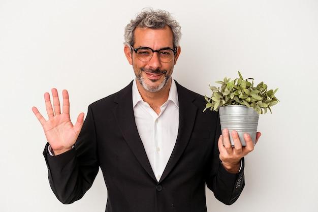 Geschäftsmann mittleren alters, der eine pflanze hält, die auf weißem hintergrund lokalisiert wird, lächelt fröhlich und zeigt nummer fünf mit den fingern.