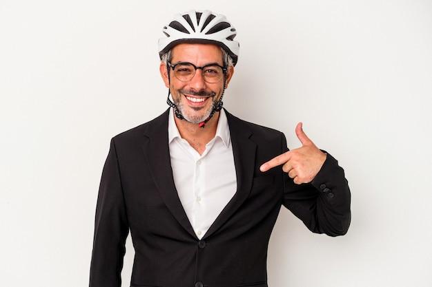 Geschäftsmann mittleren alters, der einen fahrradhelm trägt, der auf blauem hintergrund isoliert ist und mit der hand auf einen hemdkopierraum zeigt, stolz und selbstbewusst
