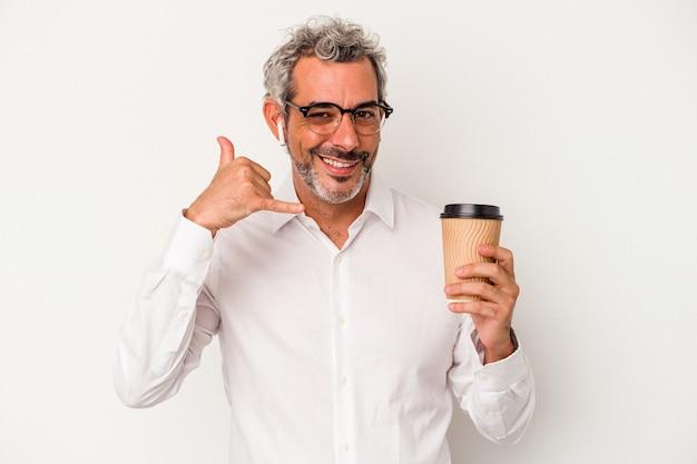Geschäftsmann mittleren alters, der einen kaffee zum mitnehmen hält, isoliert auf weißem hintergrund, der eine handy-anruf-geste mit den fingern zeigt.