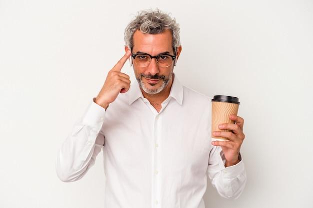 Geschäftsmann mittleren alters, der einen kaffee zum mitnehmen hält, isoliert auf weißem hintergrund, der mit dem finger auf den tempel zeigt, denkt, konzentriert sich auf eine aufgabe.