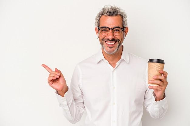 Geschäftsmann mittleren alters, der einen kaffee zum mitnehmen hält, isoliert auf weißem hintergrund, lächelt und zeigt beiseite und zeigt etwas an der leerstelle.