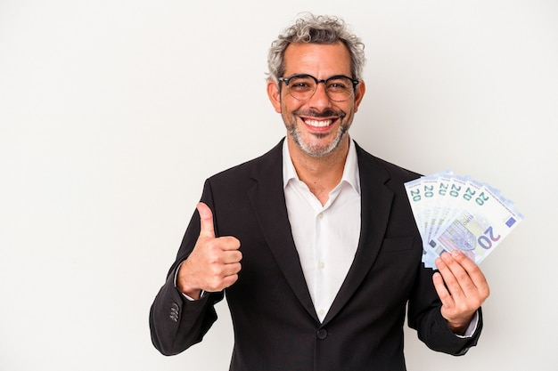 Geschäftsmann mittleren alters, der rechnungen auf blauem hintergrund isoliert hält, lächelt und hebt den daumen hoch
