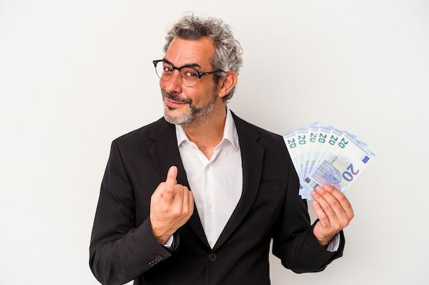 Geschäftsmann mittleren alters, der rechnungen einzeln auf blauem hintergrund hält und mit dem finger auf sie zeigt, als ob er einladen würde, näher zu kommen.