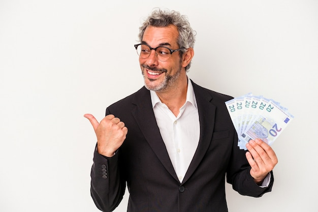 Geschäftsmann mittleren alters, der rechnungen einzeln auf blauem hintergrund hält, zeigt mit dem daumenfinger weg, lacht und sorglos.