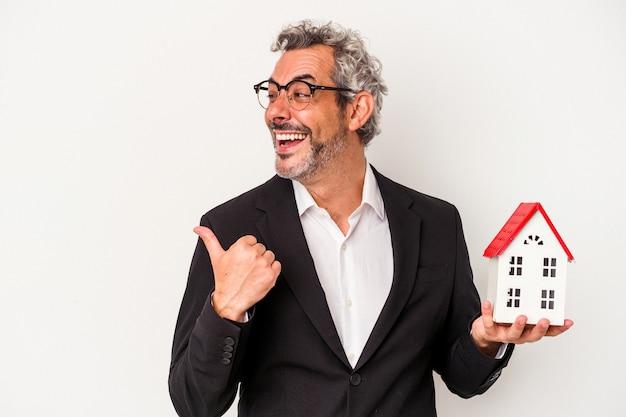 Geschäftsmann mittleren alters, der rechnungen und hausmodell einzeln auf blauem hintergrund hält, zeigt mit dem daumenfinger weg, lacht und sorglos.