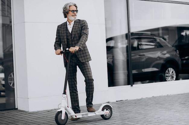 Geschäftsmann mittleren alters, der roller in einem noblen anzug reitet