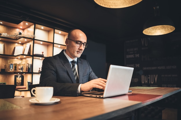 Geschäftsmann mittleren alters in der geschäftssuite und in den brillen, die mit laptop arbeiten