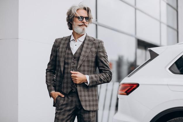 Geschäftsmann mittleren alters in einem autosalon