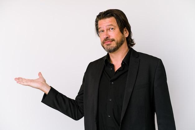 Geschäftsmann mittleren alters isoliert auf weißem hintergrund, der einen kopienraum auf einer handfläche zeigt und eine andere hand an der taille hält.