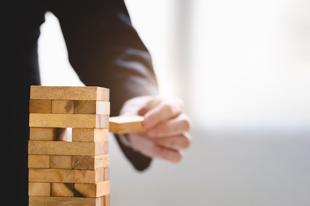 Geschäftsmann nehmen und holzklotz auf staplungsturm eigenhändig als startprojekt auswählend