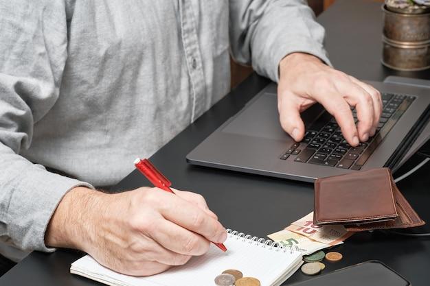 Geschäftsmann oder buchhalter, der stift hält, der am schreibtisch unter verwendung eines laptops arbeitet, um finanzbericht zu berechnen