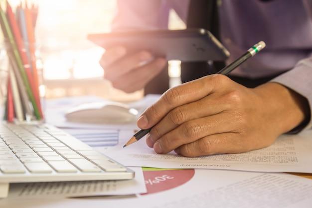Geschäftsmann oder buchhalter, die an taschenrechner arbeiten, um geschäftsdatenkonzept zu berechnen