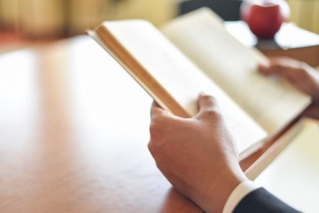 Geschäftsmann oder student, der ein buch zur hand hält - geschäftsbildungsstudienkonzeptmann, der buch auf dem tisch liest