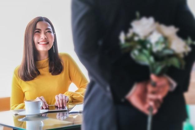 Geschäftsmann präsentiert blumen zur frau im gelben kleid im coffeeshop.