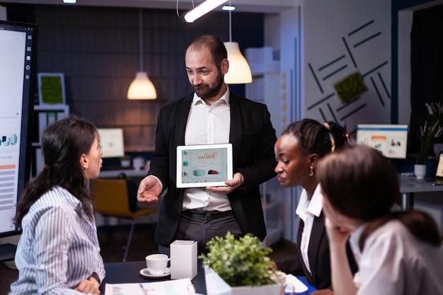 Geschäftsmann präsentiert unternehmensstatistiken mit tablet für finanzpräsentation tauchgang...