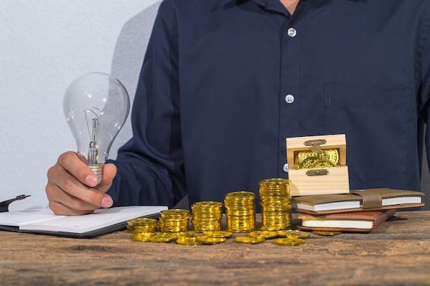 Geschäftsmann prüft kontodokumente und geldsparende ideen auf dem tisch.