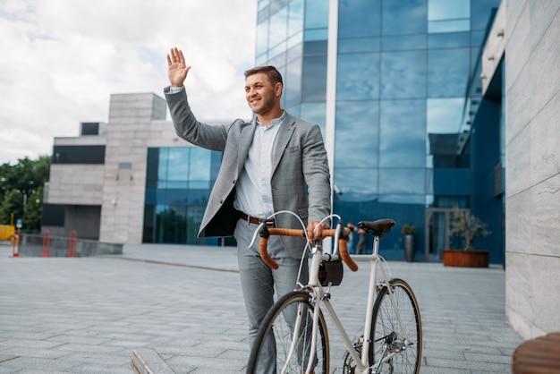 Geschäftsmann-radfahrer im anzug in der innenstadt, glasgebäude auf hintergrund. geschäftsperson, die auf öko-transport auf stadtstraße reitet