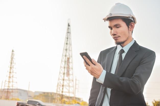 Geschäftsmann ruft handy oder mobiles smartphone auf der baustelle an