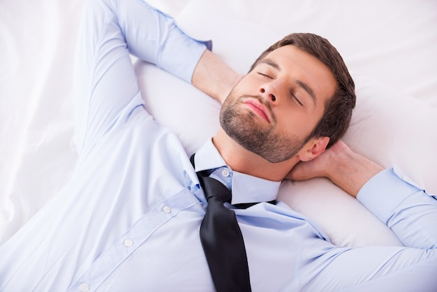 Geschäftsmann schläft. blick von oben auf einen gutaussehenden jungen mann in hemd und krawatte, der die hände hinter dem kopf hält, während er im bett schläft