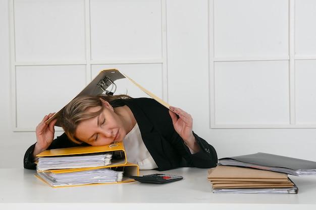 Geschäftsmann schlafend am schreibtisch mit finanzblattrechner