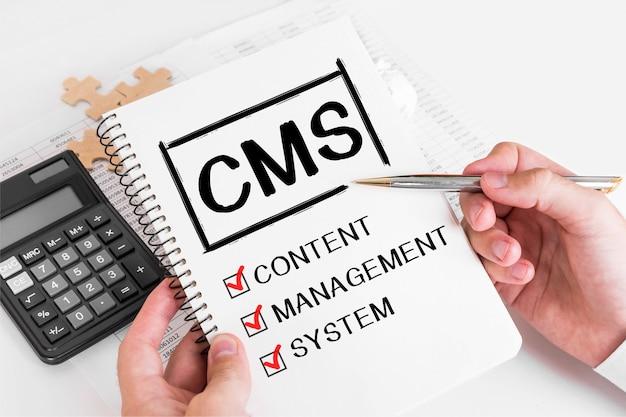Geschäftsmann schreibt cms-konzepte auf seine notiz.