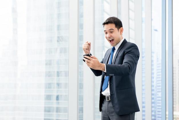 Geschäftsmann schreit und hebt seine faust mit entzücktem gefühl beim betrachten des handys