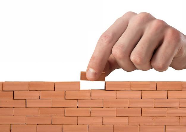 Geschäftsmann setzt einen ziegelstein, um eine große mauer zu bauen. konzept von neugeschäft, partnerschaft, integration und startup