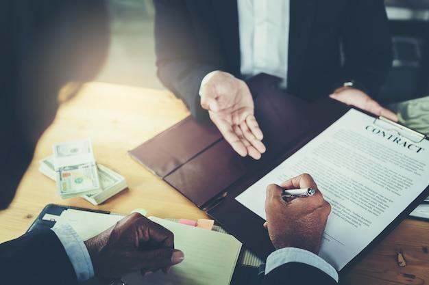 Geschäftsmann setzt unterzeichnung auf vertrag beim geschäftstreffen und beim führen des geldes nach verhandlungen