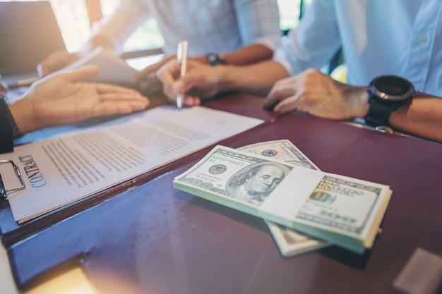 Geschäftsmann setzt unterzeichnung auf vertrag beim geschäftstreffen und beim führen des geldes.