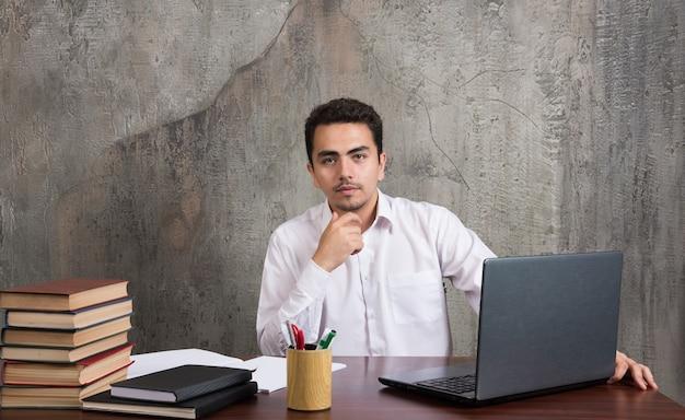 Geschäftsmann sitzt am schreibtisch mit laptop, büchern und stiften. hochwertiges foto