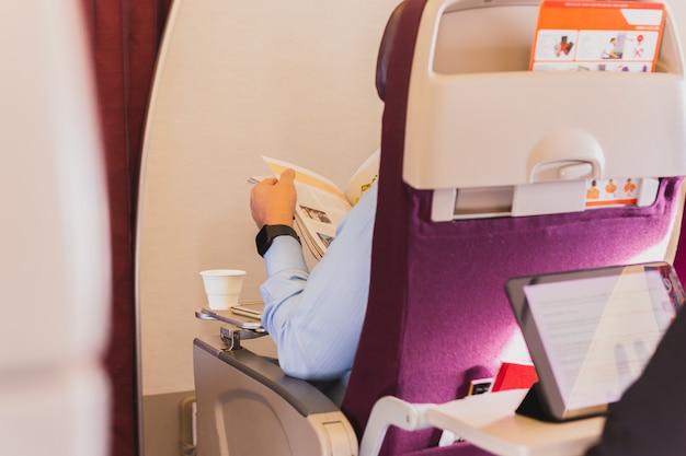 Geschäftsmann sitzt auf dem flugzeuglesemagazin mit tasse kaffee.