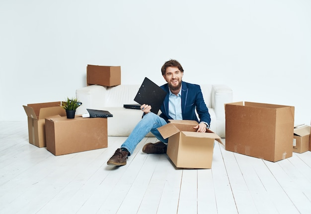 Geschäftsmann sitzt auf der couch büroleiter beim transportieren von dingen
