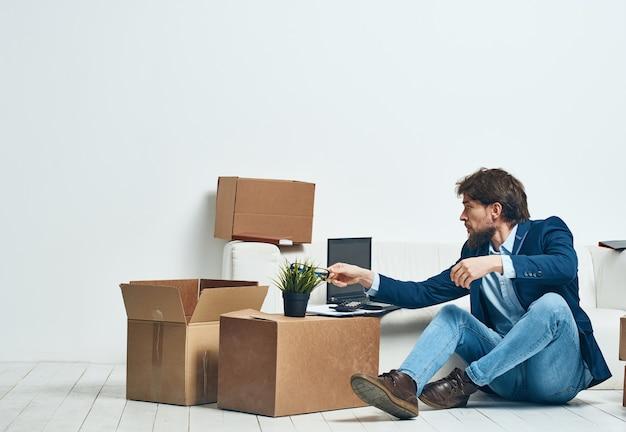 Geschäftsmann sitzt auf der couch mit laptop-boxen mit dingen, die auspacken