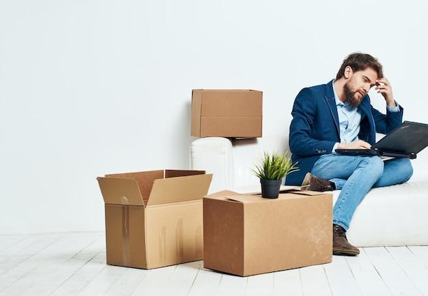Geschäftsmann sitzt auf der couch mit laptop-boxen mit dingen, die büroangestellter auspacken