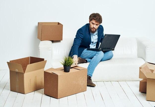 Geschäftsmann sitzt auf der couch mit laptop-boxen mit dingen, die büroangestellter auspacken.