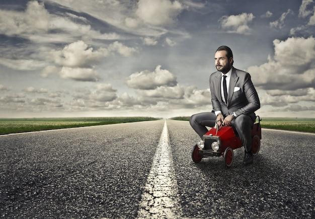 Geschäftsmann sitzt auf einem winzigen auto