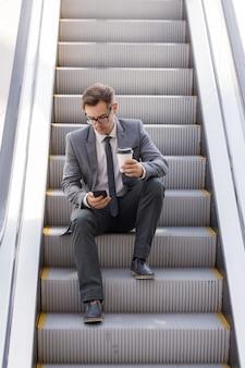 Geschäftsmann sitzt auf rolltreppe, surft im netz und hält kaffee in der hand