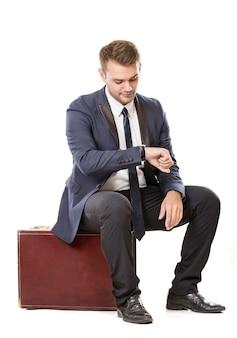 Geschäftsmann sitzt auf seinem koffer