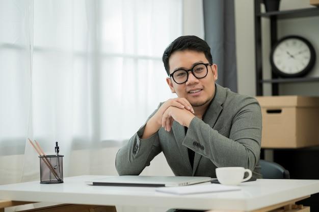 Geschäftsmann sitzt im büro nahe fenstern, die kamera betrachten.