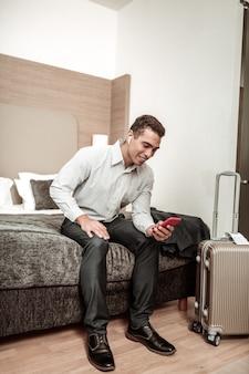 Geschäftsmann sms. junger afroamerikanischer geschäftsmann, der seiner freundin eine sms schreibt, nachdem er die jacke ausgezogen hat