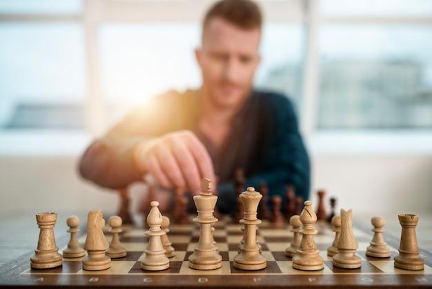 Geschäftsmann spielen mit schachspiel im büro. konzept der geschäftsstrategie und -taktik